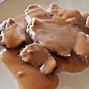 Preparación Salar los solomillos de cerdo, añadirles el tomillo u otra hierba y envolverlos en film de plástico. Colocarlos en el interior del Varoma, sin la bandeja interior. Reservar. Poner las cebollas y la papa peladas y cortadas en trozos en el vaso de la Thermomix. Programar 10 seg/vel 6. Agregar el aceite de oliva y programar 12 min/100°C/vel 1. Añadir el vino y sal a gusto y programar otros 5 min/100°C/vel 1. Añadir entonces el agua a la salsa, colocar el Varoma sobre el vaso y programar 15 min/Varoma/vel 3. Abrir el Varoma e intercambiar la posición de las piezas de carne, ya que la zona en la que se tocan entre ellas tarda más en cocinarse que los bordes. Volver a programar 15 min/Varoma/vel 3. Sacar las piezas de carne del Varoma y comprobar que están hechas por dentro, para eso hacer un pequeño corte. Verter en el vaso los jugos que hayan quedado en el film de plástico y reservar al calor. Si al añadir los jugos de la carne la salsa queda demasiado líquida, volver a programar otros 5-10 minutos/Varoma/vel 3, hasta reducirla a la consistencia deseada. Una vez reducida la salsa, programar 30 seg/vel 9 para triturarla completamente. Servir la carne fileteada con la salsa caliente aparte. Consejos Este método de cocinar piezas de carne al vapor en el Varoma da su mejor resultado con piezas que no sean muy grandes, que se cocinan de forma más homogénea. La salsa de esta carne en salsa con Varoma se puede variar a gusto, añadiendo hortalizas más variadas o distintas, y usando otro líquido distinto del vino dulce.